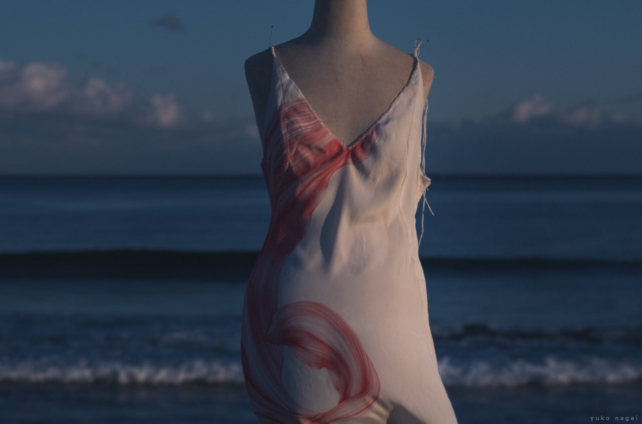 A hand painted flower dress on the shore.