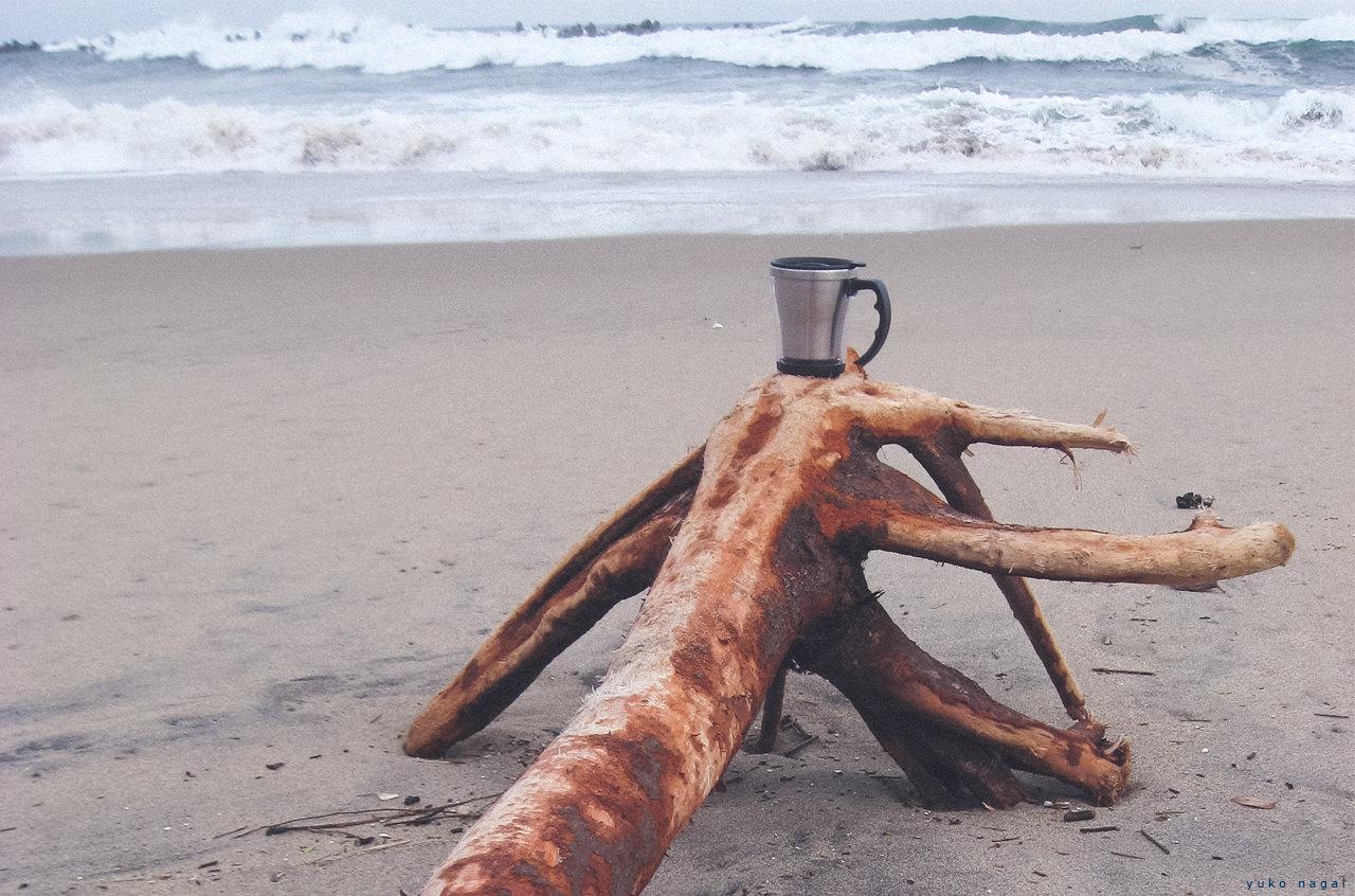 A coffee cup on a beach driftwood.