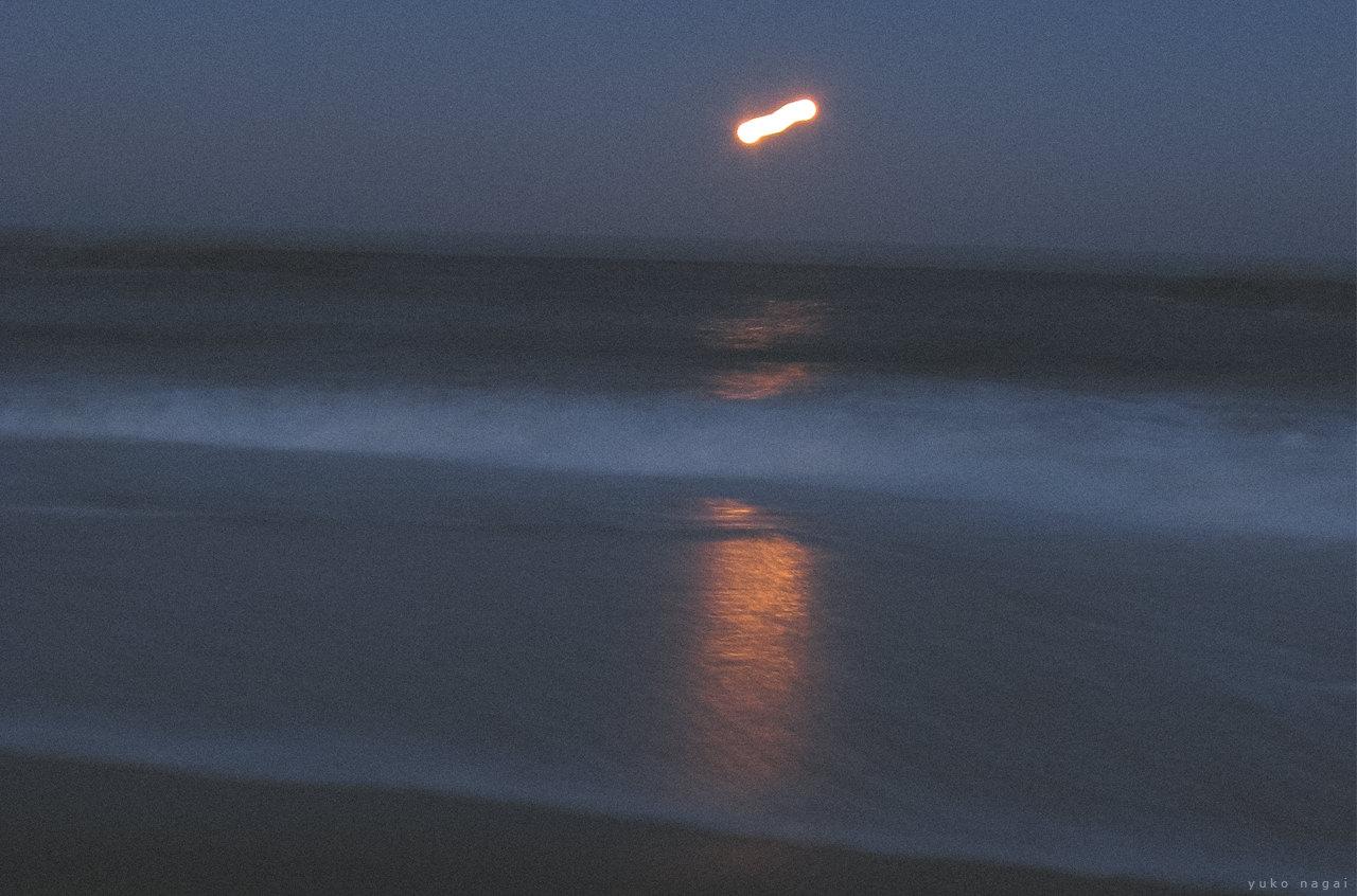 Moon above shore.