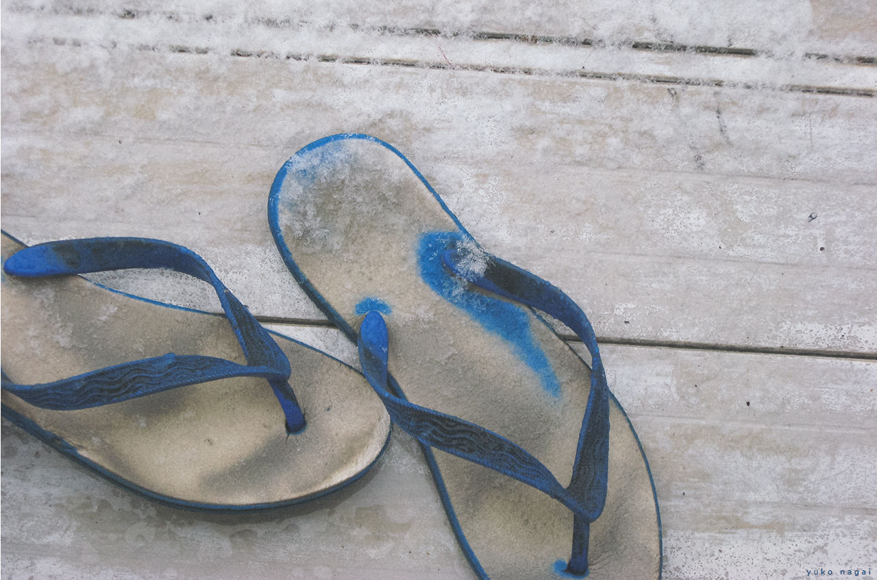 Worn sandals frosted with snow.