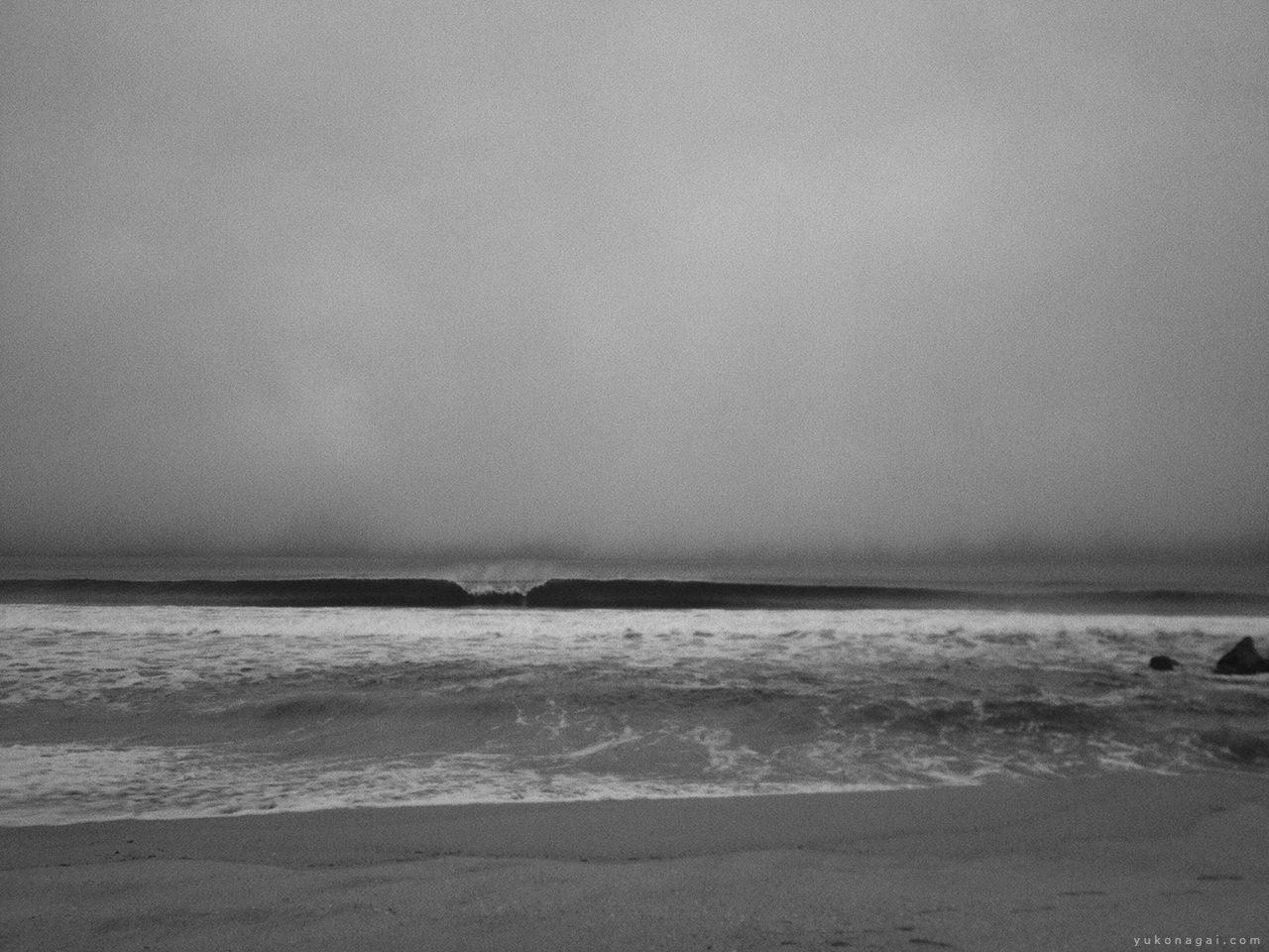 A wave on a cloudy beach.