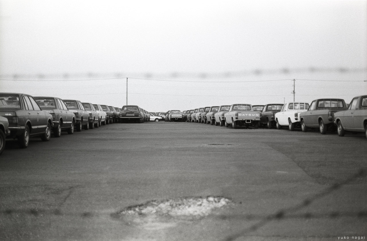 Auto mobiles in a fenced parking lot.