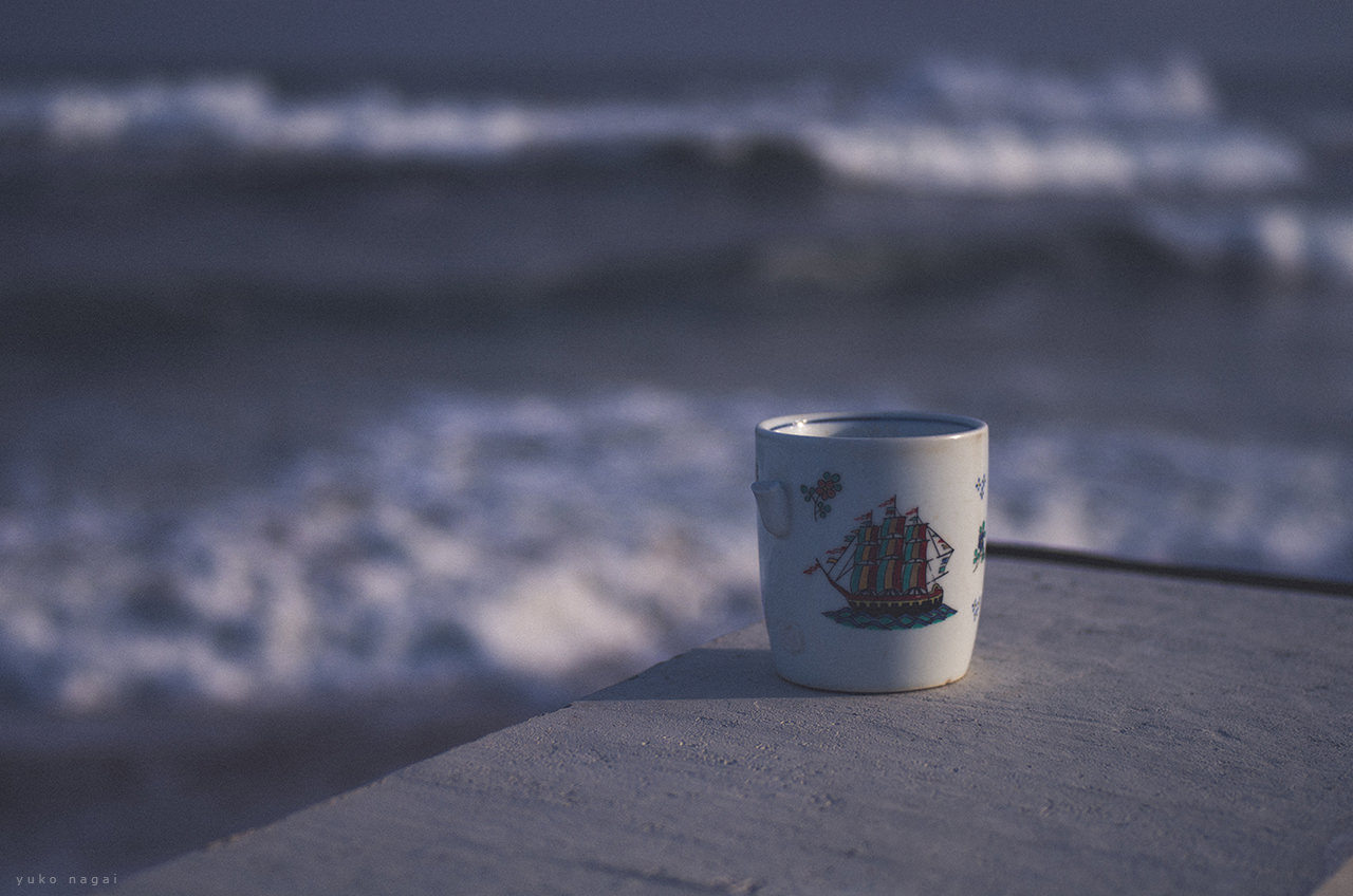 A coffee cup by the ocean.