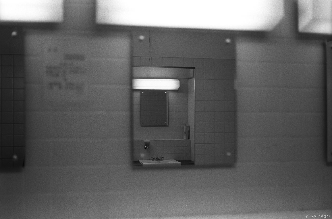 Mirrors facing each other in a dimly lit rest room.