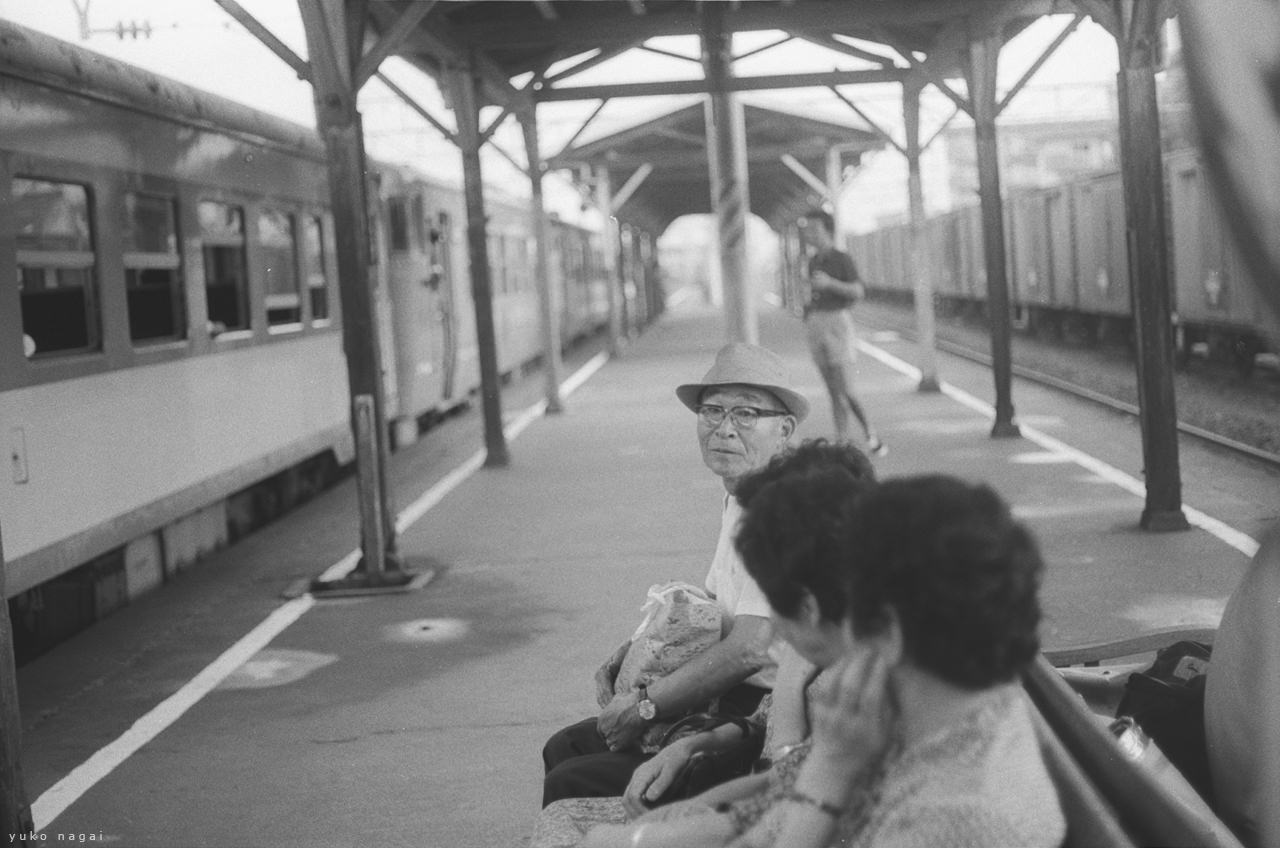 A group of seated people on a train station platform.