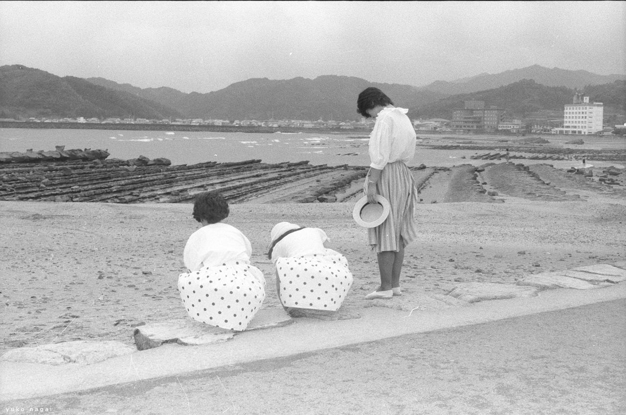 Three Girls in matching white blouse on the beach.
