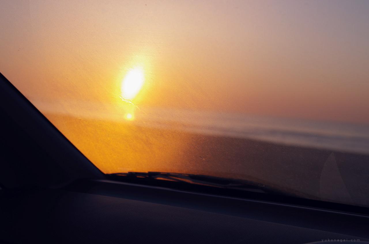 Sunrise on the beach from a car window.