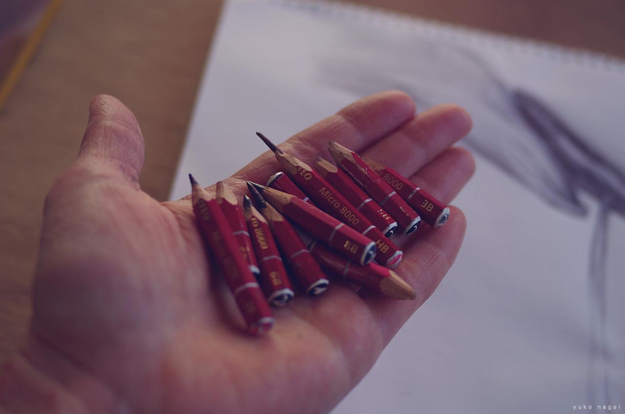 Pencils on artist's hand.